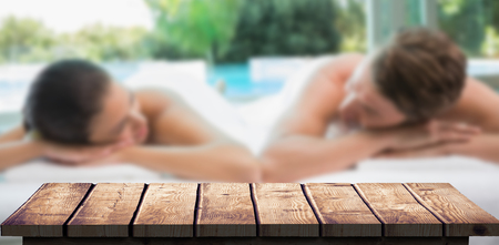 massage  table: Couple lying on massage table at spa center against wooden floor