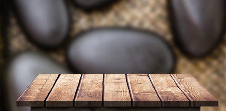 Suelo de madera contra un montón de piedras negras Foto de archivo