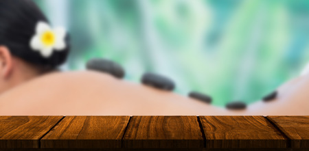 hot stone: Beautiful brunette enjoying a hot stone massage against wooden desk