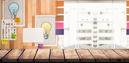 attached: Light bulb charts attached on wooden wall against wooden desk
