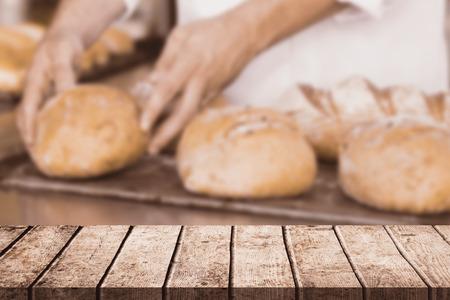 hotel staff: Wooden table against baker checking freshly baked bread Stock Photo