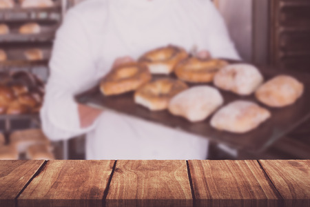 roll out: Wooden table against happy baker showing tray of fresh bread