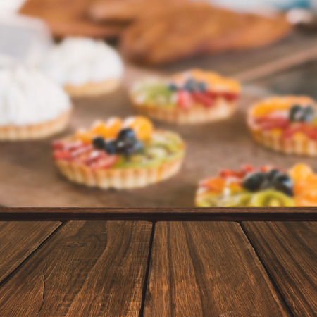 cafeteria tray: Close-up of wooden flooring against tray of sweet pastry tarts Stock Photo