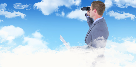 using binoculars: Businessman using binoculars against blue sky