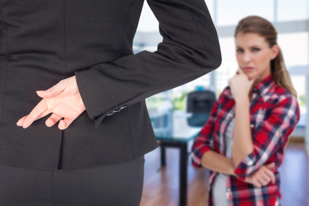 Businesswoman with fingers crossed behind her back against board room