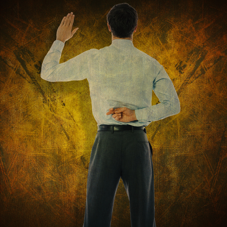 crossing fingers: Businessman crossing fingers behind his back against dark background
