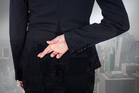 Businesswoman with fingers crossed behind her back against city skyline Фото со стока