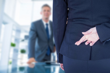 Businesswoman with fingers crossed behind her back against business people looking at camera behind desk Фото со стока