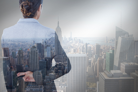 Businesswoman with fingers crossed behind her back over white background against city skyline Фото со стока