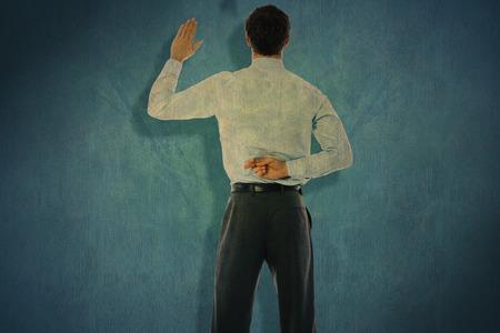 crossing fingers: Businessman crossing fingers behind his back against blue