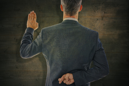 an oath: Rear view of businessman taking oath with fingers crossed against bleached wooden planks background Stock Photo