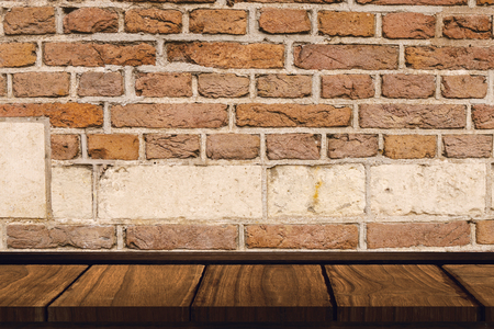 red brick wall: Wooden desk against red brick wall