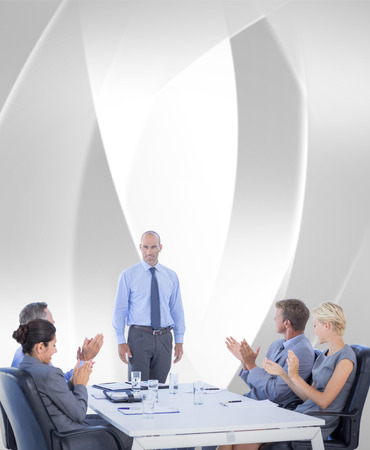 angular: Business people applauding during meeting  against white angular design