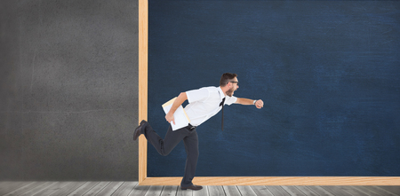 running late: Geeky young businessman running late in front of a chalkboard