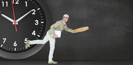 rushing hour: Happy delivery man running in front of a clock on a black room