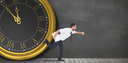 running late: Geeky young businessman running late in front of a clock Stock Photo
