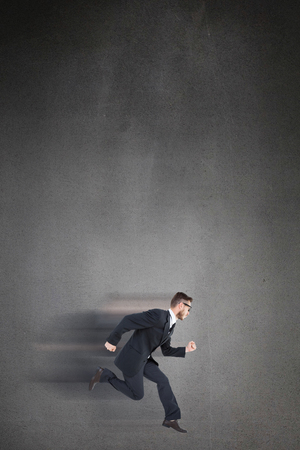 mid air: Geeky young businessman running mid air on black background Stock Photo