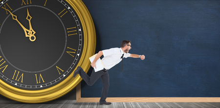 running late: Geeky young businessman running late in front of a clock and a chalkboard Stock Photo