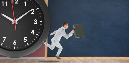 Businessman running in front of a clock and a chalkboard