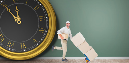 delivery room: Happy delivery man with trolley of boxes running in front of a clock on green room