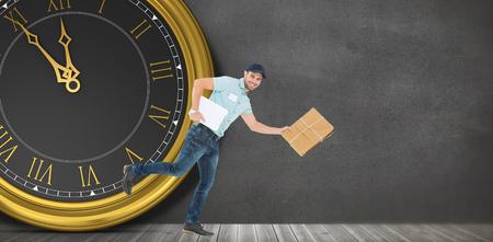 sala parto: uomo di consegna felice che funziona con il pacchetto di fronte a un orologio in una stanza grigia Archivio Fotografico