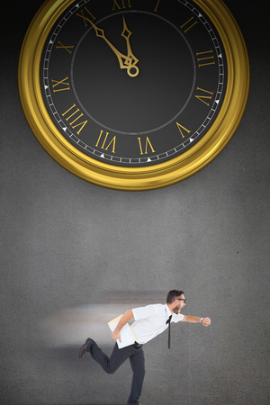 running late: Geeky young businessman running late on a grey background with a clock