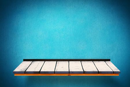 blue wall: Wooden shelf against blue wall