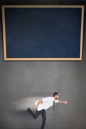 running late: Geeky young businessman running late on grey background with a black board