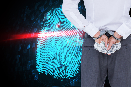 restraining device: Businessman in handcuffs holding bribe against digital security finger print scan