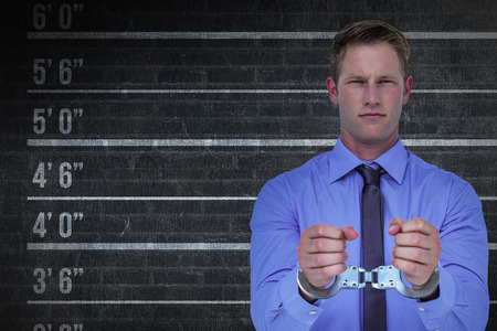 restraining device: Handsome businessman wearing handcuffs against digital composite image of height measurement Stock Photo