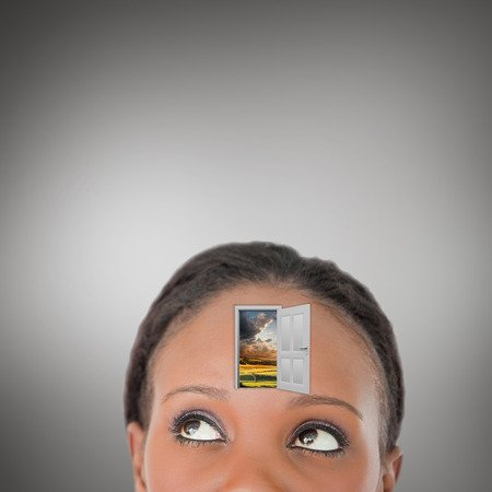diagonally: Close up of woman looking upwards diagonally with a door on her forehead