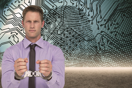 restraining device: Handsome businessman wearing handcuffs against fingerprint with circuit board graphic