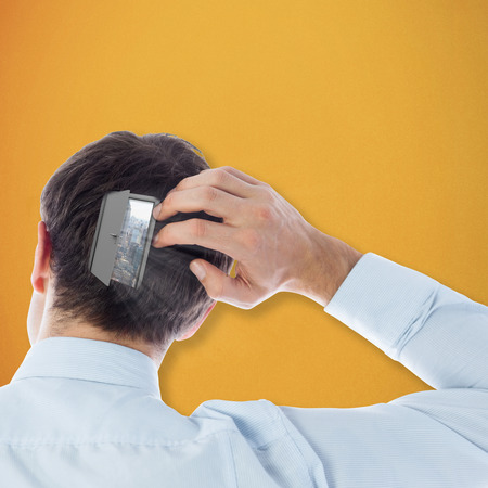 scratching: Businessman scratching his head against orange background Stock Photo