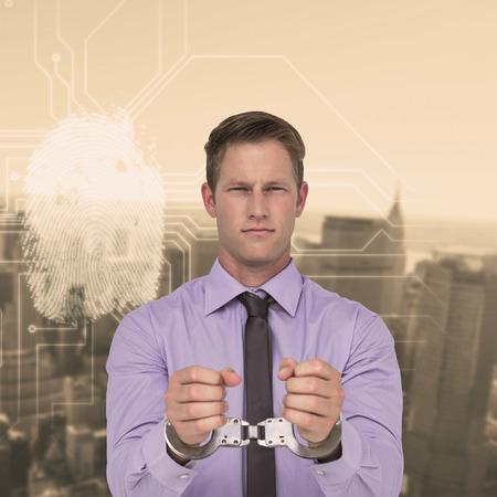 restraining device: Handsome businessman wearing handcuffs against new york skyline