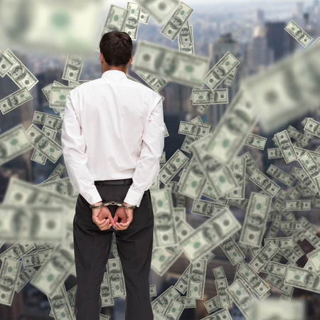 restraining device: Rear view of young businessman wearing handcuffs against view of cityscape Stock Photo
