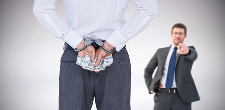 restraining device: Businessman in handcuffs holding bribe against grey background