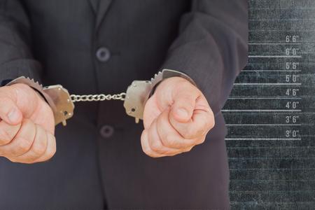 restraining device: Handcuffed businessman against mug shot background