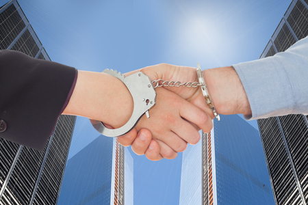 restraining device: Business people in handcuffs shaking hands against skyscrapers Stock Photo