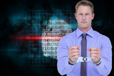 restraining device: Handsome businessman wearing handcuffs against digital security finger print scan Stock Photo