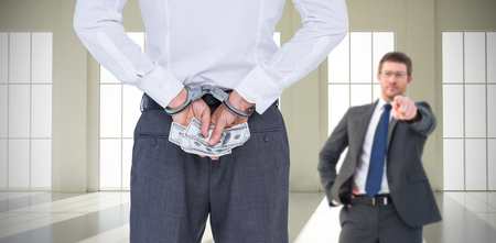 Businessman in handcuffs holding bribe against room with windows