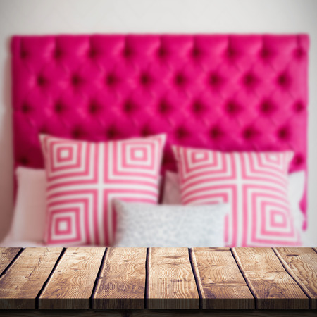 duvet: Wooden table against a bed with pillow