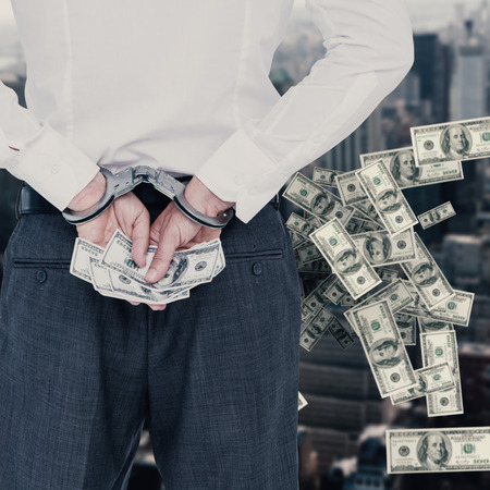 restraining device: Businessman in handcuffs holding bribe against view of cityscape Stock Photo