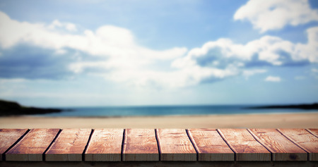 wooden desk: Wooden desk against beach with blue sky Stock Photo