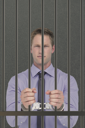 interned: Handsome businessman wearing handcuffs against grey background