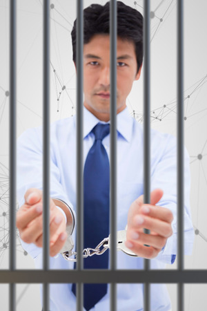 interned: Portrait of a businessman with handcuffs against black lines on grey background Stock Photo