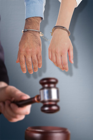 restraining device: Closeup of handcuffed business people against digital image of gray wall