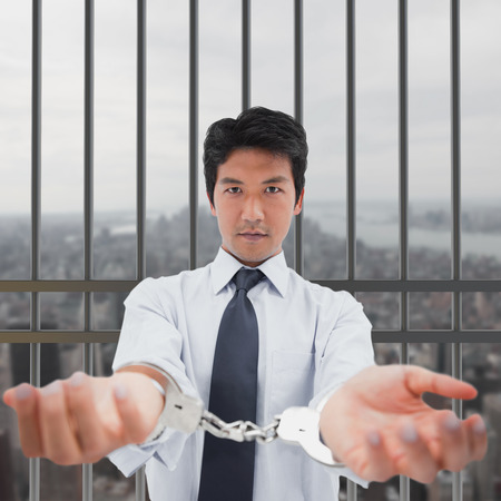 interned: Businessman with handcuffs against new york