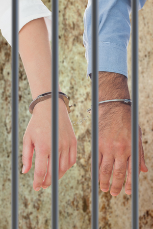 interned: Closeup of handcuffed business people against dirty old wall background Stock Photo