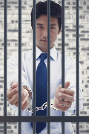 interned: Portrait of a businessman with handcuffs against grey brick wall Stock Photo