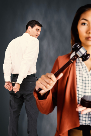 Businesswoman banging a law hammer on the gavel against dark background Stock Photo